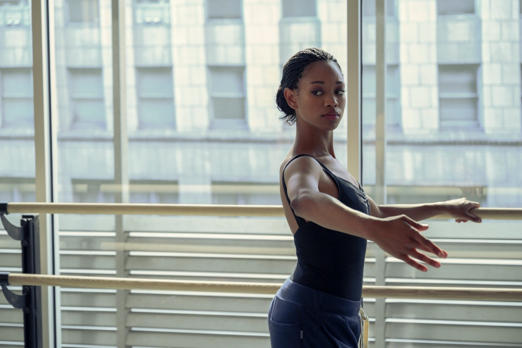 Kylie Jefferson as Neveah Stroyer. She is dressed in her rehearsal ballerina gear, a black strappy body suit and dark blue sweatpants. She holds a bar and is poised