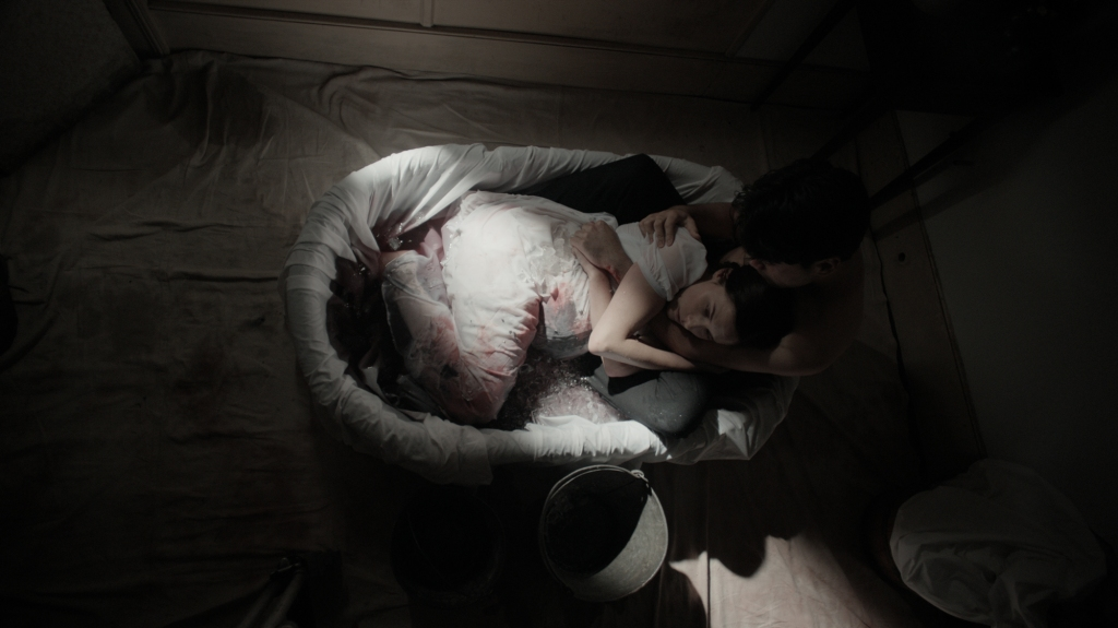 A still from 'A Nightmare Wakes'. Mary Shelley is being cradled in a bathtub by her husband Percy. the small bathtub is covered in linens and filled with ice. Mary is heavily pregnant and her white nightdress is covered in blood.