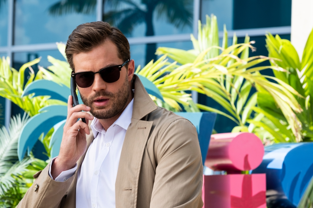 Still from 'Barb & Star Go to Vista Del Mar' - Jamie Dornan wearing a tan trench coat, a white shirt, dark sunglasses. He is holding up a phone talking to someone while standing ourdoors.