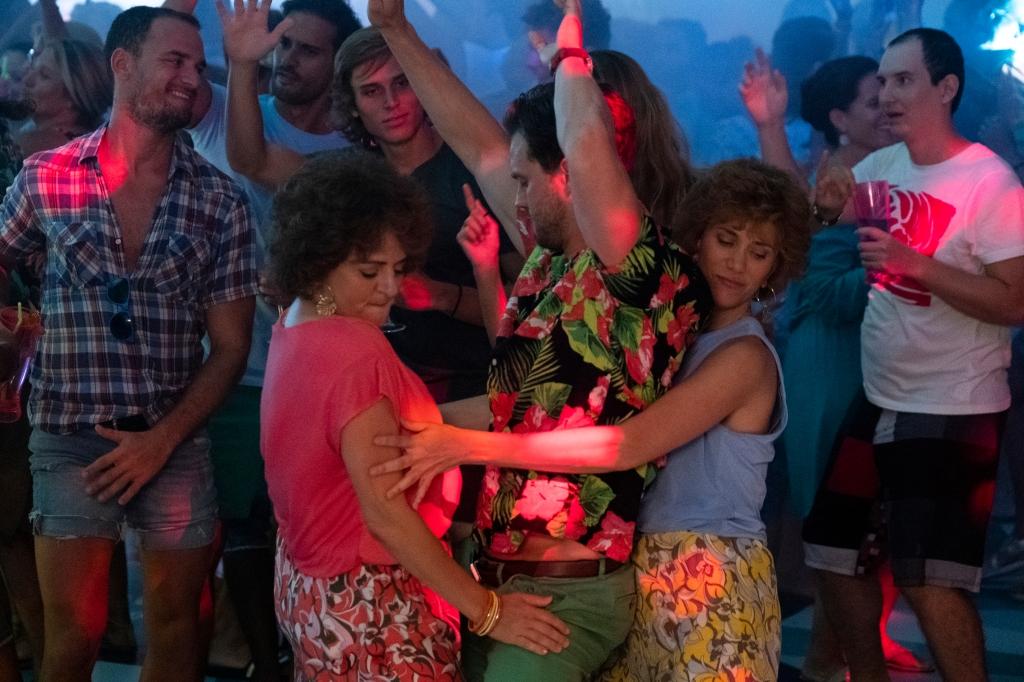 Still from 'Barb & Star Go to Vista Del Mar' - Annie Mumolo, Jamie Dornan, and Kristen Wiig dancing in a club. Dornan sandwiched between Mumolo and Wiig.