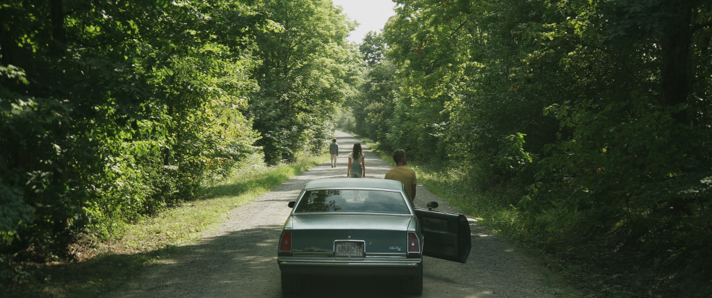 A still from 'Butchers'. A broken down car in the middle of a wooded road is shown in a wide shot. Three young people have their backs to the camera, scattered down the road, looking forward. It is a summer's day.