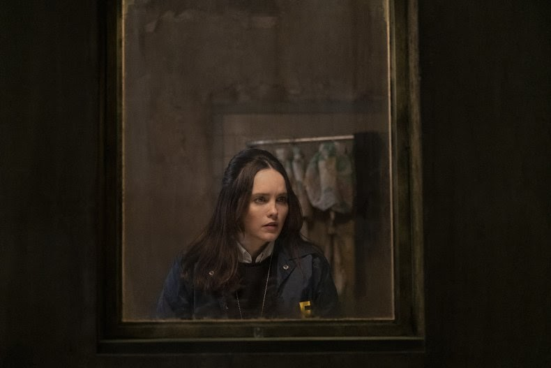 A still from TV show 'Clarice'. Clarice Starling (Rebecca Breeds) is shown though the window of what is likely a prison cell. She is peering into the cell, wearing her FBI uniform. Her hair is long and dark, she is white with dainty features, very petite. The scene is grimy and dark.