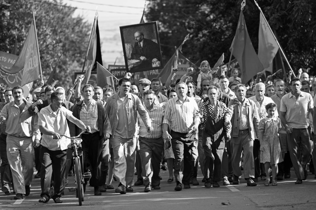 A black and white still from 'Dear Comrades'. A scene of protest. A large group of mainly men fill the frame, marching with flags and raised fists in communist Russia.