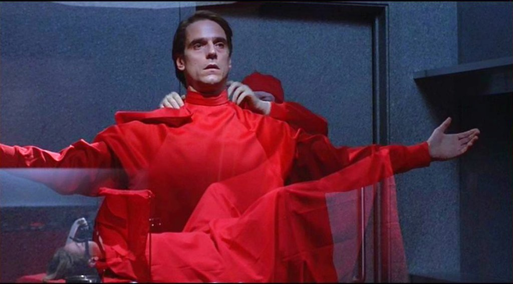 A still from 'Dead Ringers'.  Elliot Mantle (Jeremy Irons)  is shown getting into his bright red surgical gown, he is being dressed by another surgeon. His arms are outstretched.