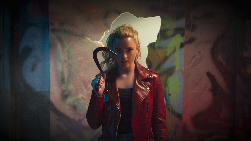 A still from 'Freaky'. Millie Kessler (Kathryn Newton) is shown mid-shot, centre frame, holing a bloody hook. She stands against a graffiti backdrop with a hole ripped out, of which she stands in front of. Millie is a teenage girl, white, with blond hair in a ponytail and minimal makeup. She wears a blood red leather jacket and black vest top underneath. She looks directly down the camera.