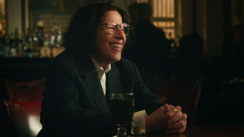A still from TV Show 'Pretend It's a City'. Fran Lebowitz is sat at a table with a drink, her hands clasped in front of her, smiling. She has a large smile, dark chin-length hair and tortoise shell glasses.She wears a plaid suit and white shirt.