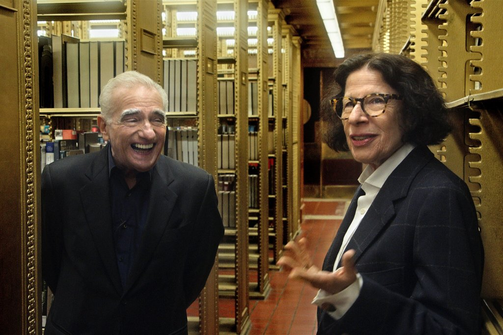 A still from 'Pretend its a City'. Fran Lebowitz is stood in an archive with Martin Scorsese, he is laughing at what she is saying.