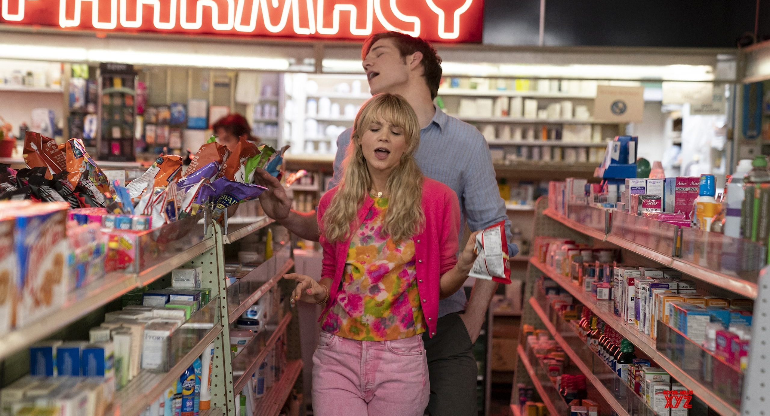 Bo Burnham and Carey Mulligan in 'Promising Young Woman'. They are walking down an isle in a drugstore, singing along to a song.