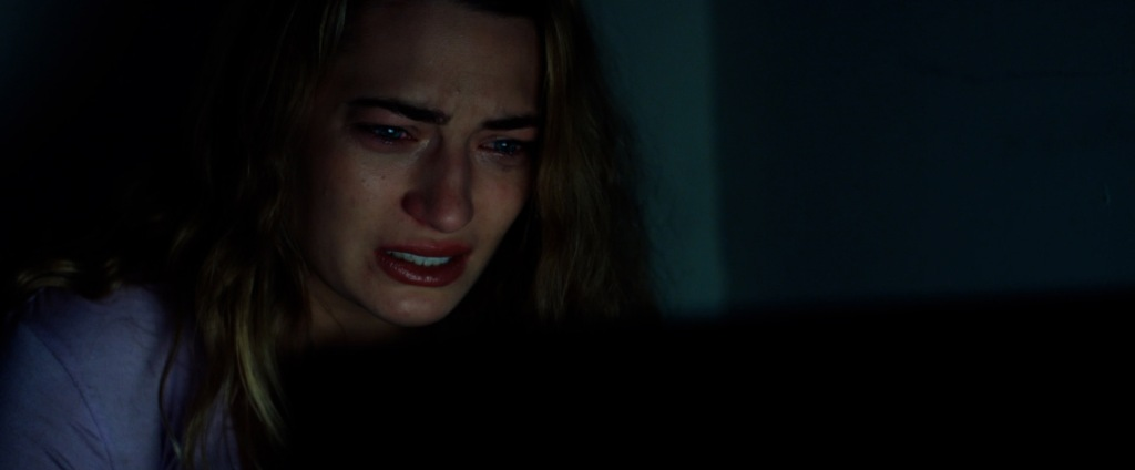 A still from 'Shook'. Mia (Daiyse Tutor) is shown in close-up to the left of the image. She is a blonde, young white women and is scrunching her face up, tears in her eyes, reading a message on her laptop.