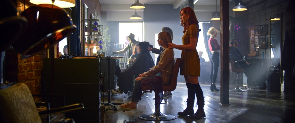 A still from 'The Stylist'. Claire (Najarra Townsend) is shown in a wide shot, working in a busy salon. Sh eis touching a clients hair and mid-speak. Claire is wearing a short mustard coloured dress, knee high socks and combat boots. Her hair is red, shoulder length and waved. The scene is bustling with other stylists and clients.