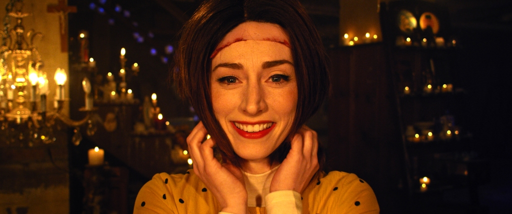 A still from 'The Stylist'. Claire (Najarra Townsend) is shown in close-up, centre frame. She is wearing another woman's scalp on top of her head, with chin length straight brown hair framing her wide smile. Claire is in a room lit my candles and chandeliers, her smiling face shining through as her hands clutch the hair around her face with pride.
