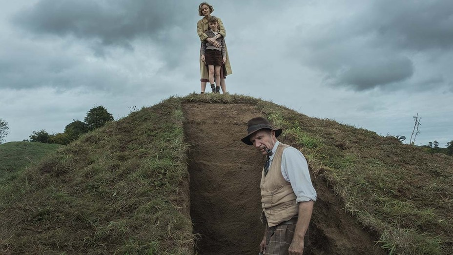 A still from 'The Dig'. Basil (Ralph Fiennes) is stood at the base of an excavation, smoking a pipe. He is wearing 1930s clothing: tweed pants, white linen shirt and a beige waistcoat with a hat. At the top of the dig mound is Edith (Carey Mulligan) and her son, she is clutching him from behind, looking down into the site.