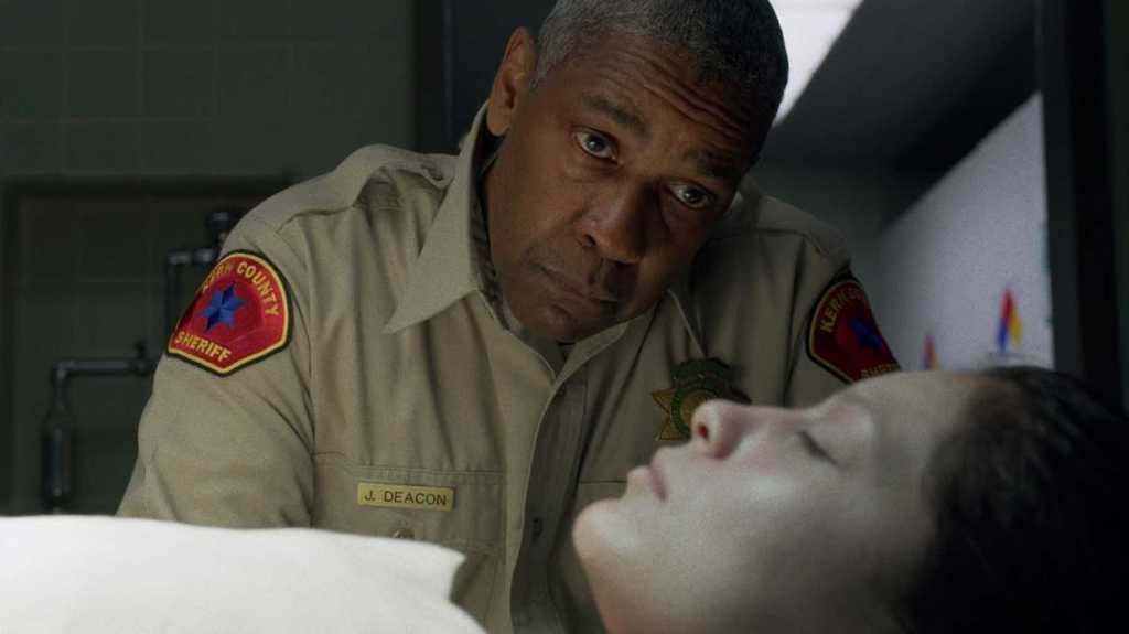 Denzel Washington as Deke in 'The Little Things'. Dressed a county deputy leaning over a female corpse in a police department morgue. Deke has a sorrowful expression on his face as he gazes upon the victims face.