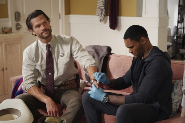 A still from 'Walker'. Cordell (Jared Padalecki) is shown sat on a red sofa with Trey (Jeff Pierre), who is wearing blue gloves and cleaning a wound on Cordell's hand. Cordell is a white man in his 30s wearing a Texas Ranger uniform, minus the jacket and stetson. Trey is a Black man in his 30s with close cropped hair, wearing dark jeans and a dark hoodie.