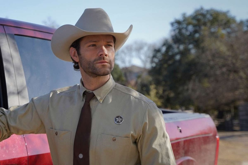 A still from 'Walker'. Cordell Walker (Jared Padalecki) is shown in close-up to the left of the image. He is wearing a texas ranger uniform and stetson. He is in his 30s, white with dark hair slicked under his hat and a closely shaved beard.