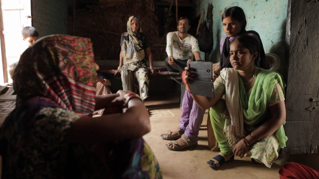 A still from documentary 'Writing with Fire'. An Indian woman sits holding her smartphone, filming another woman. there are 5 other people in the room, men and women, watching the interview take place.