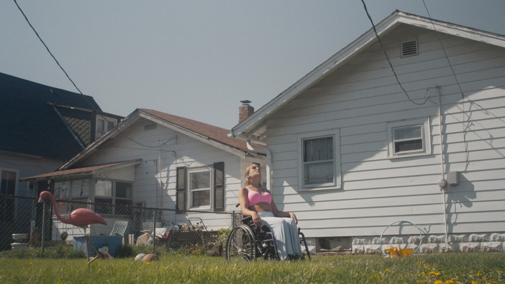 Shot from Crossroads of America. A young woman sits back in a wheelchair, topless with a pink bra on in a back garden. White, wooden slatted houses sit behind her seperated by a chain fence. There are flowers growing in the overgrown grass and she is looking up into the sky.