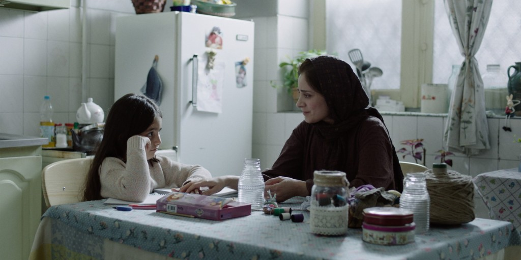Still from Ballad of a White Cow. Mina (Maryam Moghaddam) and her daughter Bita (Avin Purraoufi) are sitting at a kitchen table - it is covered in empty jars and craft materials. Mina has a hand stretched out towards Bita and is looking at her lovingly, while Bita rests her head on her hand and stares back.