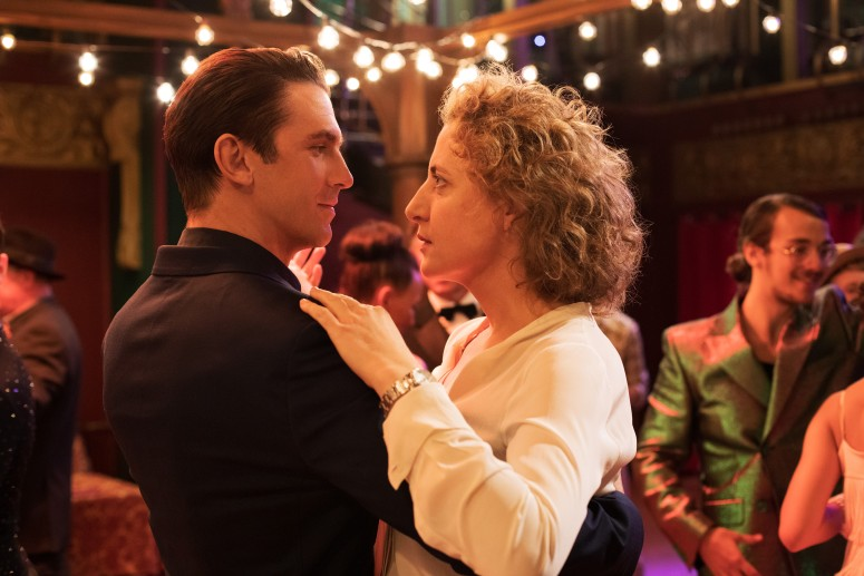 Still from I'm Your Man. Dan Stevens (Tom) and Maren Eggert (Alma) hold each other in a dancing pose, bodies close to other.  Tom has a confident smile on his face while Alma looks more nervous. There are couples dancing in the background and white fairy lights hang from the ceiling.