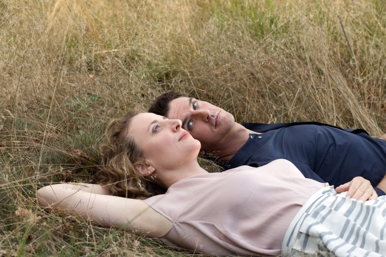 Tom and Alma lie on the grass in a field. Alma is staring up at the sky with a arm stretched behind her head as a pillow. Tom stares at her, interested, his body close to hers but angled away slightly.