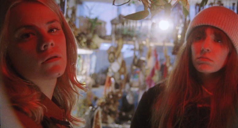 Still from The Scary of Sixty-First. Dasha Nekrasova (the mystery woman) is on the left, looking almost directly at the camera, while Madeline Quinn (Noelle) is on the rihgt hand side, looking at her. They are in shop filled with mystic inventory hanging from all walls. They are bathed in a red light.
