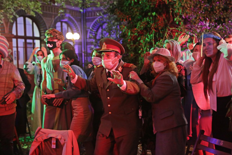 A group of parents, all wearing different face masks, and outfits hold out their hands, reacting to something off screen. They are bathed in red light, and in the background there are trees.