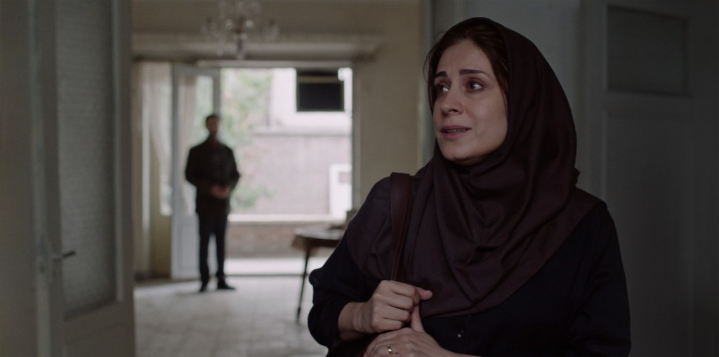 Still from Ballad of a White Cow. Maryam Moghaddam (Mina) stands in the foreground visibile from her chest updates. She is wearing a dark coloured-hijab and is looking offscreen. In the background, the out of focus figure of a man watched from the room behind her.