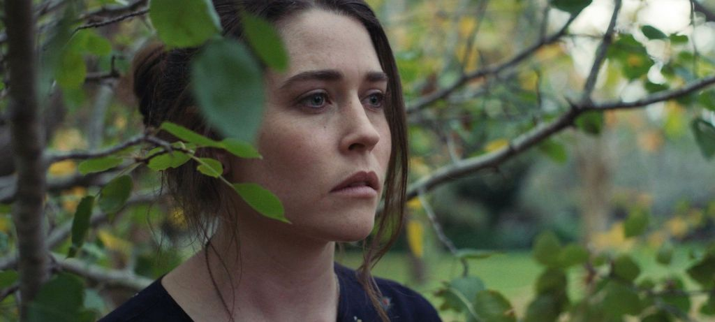 Jane Watt, as Beth in The Greenhouse. A young woman with brown hair tied back, but with strands falling around her face, stands in greenary. Leaves frame her face as she looks into the distance, grief and sadness clear on her face.