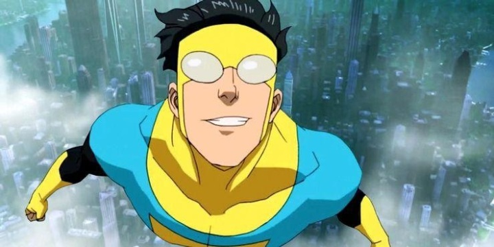 A still from cartoon TV show 'Invincible'.  Mark Grayson (voiced by Steven Yuen) is shown centre frame, flying above a city skyline in a blue and yellow supersuit. His dark hair pokes out of the top and flies in the wind.