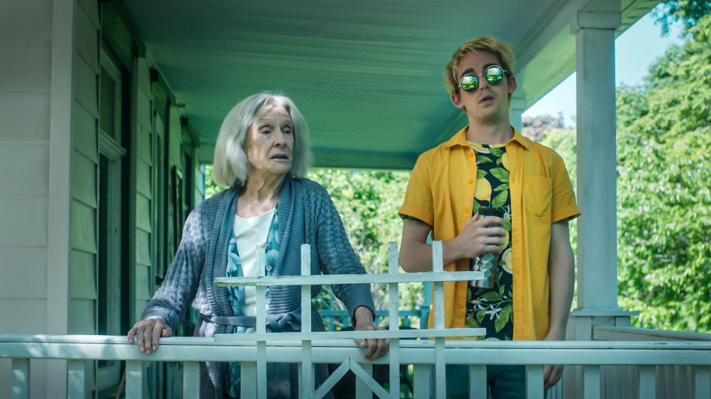 Cloris Leachman and Thomas Duplessie stand on a back porch of a house, mid-conversation. Duplessie is wearing a bright yellow shirt over, with a black t-shirt covered in lemons underneath - he is wearing reflective sunglasses and looking hungover. Leachman is wearing a casual blue cardigan.