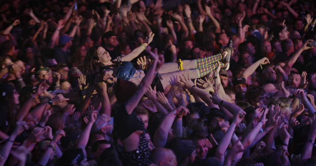 A still from documentary 'Long Live Rock'. A girl is shown corwd surfing on her back through a mosh pit. Everyone's arms are outstretched, she is in a state of euphoria.