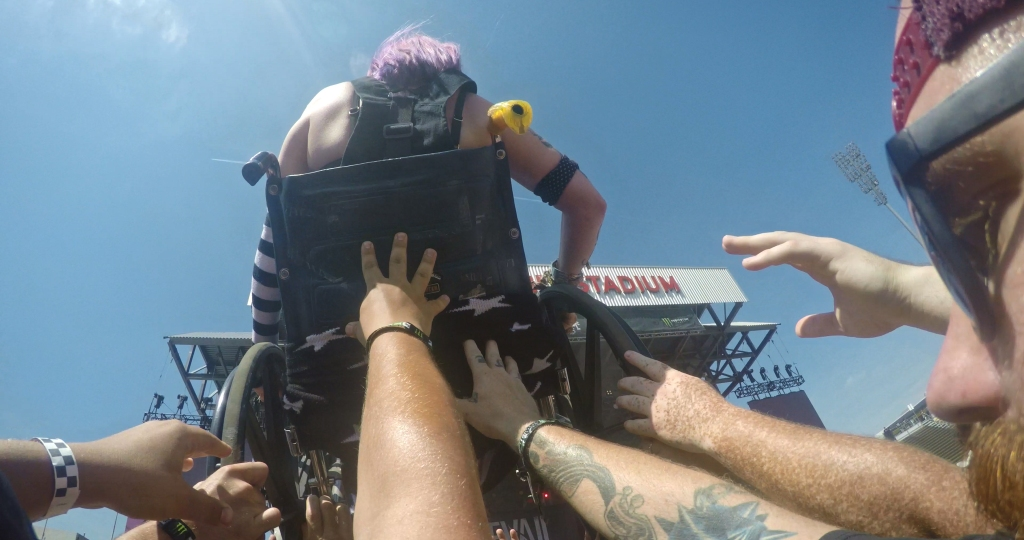 A still from documentary 'Long Live Rock'. a young girl in a wheelchair is shwon from the back being lifted above a crowd in a mosh-pit.