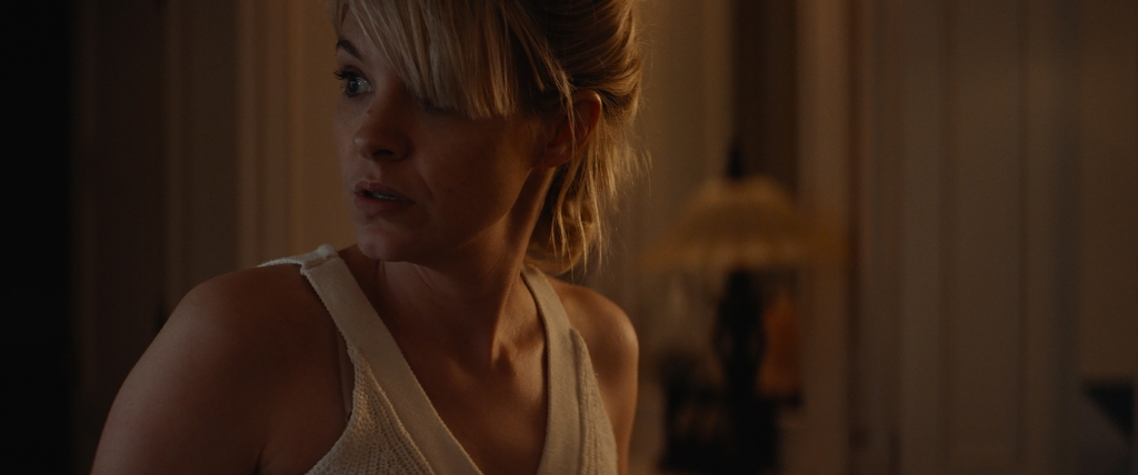 A still from 'Lucky'. May (Brea Grant) is shown in close-up, in her dimly lit house, to the left of the image, she is looking back over her shoulder in fear. She is wearing a white strappy top, she is a blonde woman in her 30s, her fringe covering half her face, and a mole on her nose. Her lips are apart in shock.