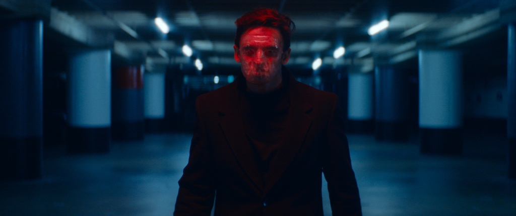 A still from 'Lucky'. The Man is shown centre frame, in close-up, in a blue-lit parking garage. He is wearing a clear plastic mask that blurs his facial features. He is wearing a black wool smart jacket, black top and has dark cropped hair.