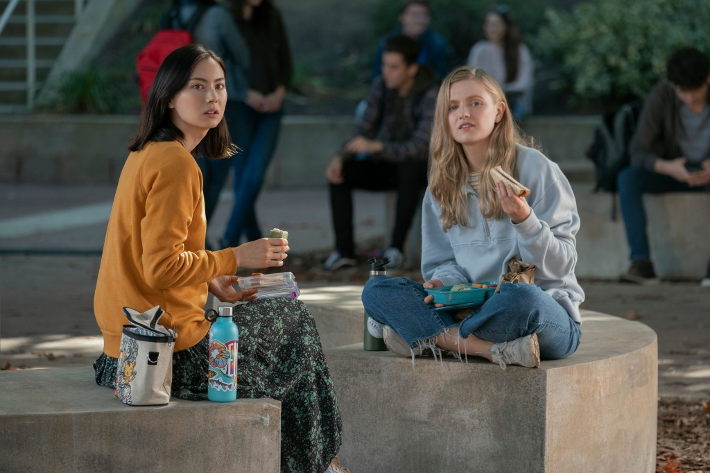 Lauren Tsai as Claudia and Hadley Robinson as Vivian in Moxie. The two sit on a concrete-made outdoor seating area on school campus. They both are eating lunch but ar glancing away at their food as the look at something they are discussing.