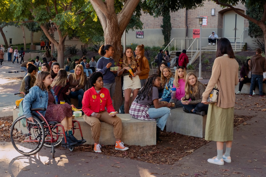 Emily Hopper as Meg, Anjelika Washington as Amaya, Sydney Park as Kiera, Sabrina Haskett as Kaitlynn, Alycia Pascual-Peña as Lucy Josie Totah as CJ, Hadley Robinson as Vivian, Lauren Tsai as Claudia in Moxie. They all are seated on concrete made seating as a few stand by a tree planted at the centre. Most of the girls gaze at Claudia who stands out side of the seating area speaking to Vivian.