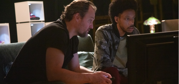 A still from 'Silk Road'. Rick Bowden (Jason Clarke) is shown sitting on a sofa with another man, both of them looking at a television screen.