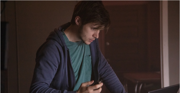 A still from 'Silk Road'. Ross Ulbricht (Nick Robinson) is shown in a mid-shot, centre frame, he is holding a phone in one hand and is looking down to his laptop which you can only partly see in the image. He is a young white man in his twenties with short dark hair, minimal facial hair and wearing a green t-shrit and blue hoody.