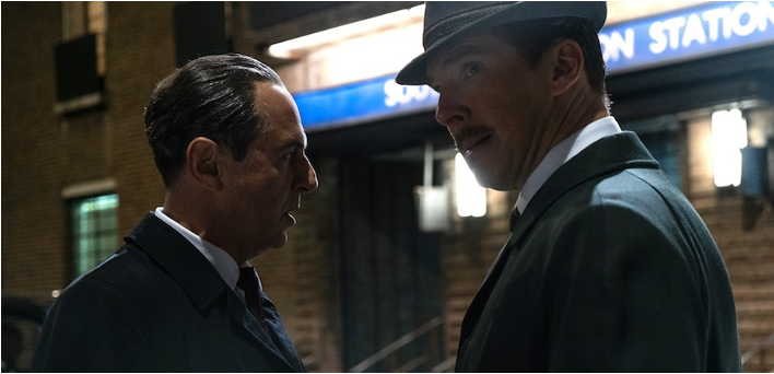 A still from 'The Courier'. Greville Wynne (Benedict Cumberbatch) is standing on a street with another gentleman. they are shot in close-up it looks like they are trying to exchange information without gaining attention. It is 1960s set.