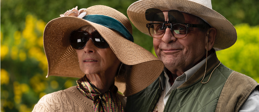 A still from 'The Owners'.  Mrs. Huggins (Rita Tushingham) and Dr. Huggins (Sylvester McCoy) are shown in close-up, standing next to each other, in a garden. They are an eldery, wealthy white couple. both wearing straw sun hats and glasses, Mrs Huggins wears a silk necktie and Dr. Huggins wears a quilted gilet, he smirks.