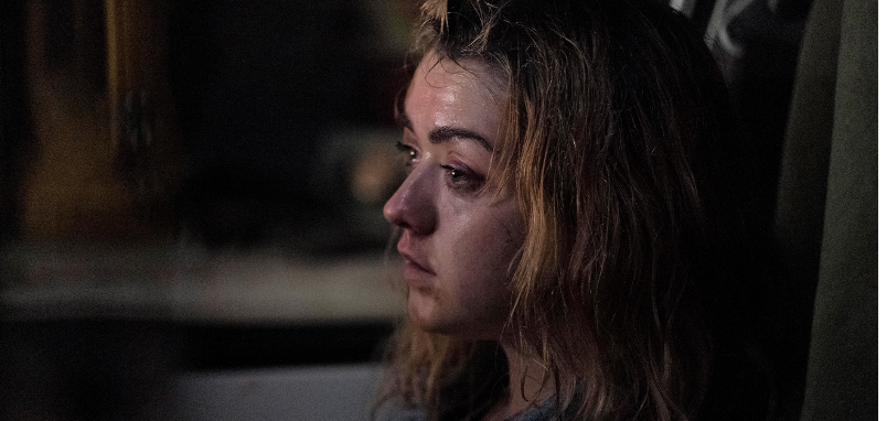 A still from 'The Owners'. Mary (Maisie Williams) is shown in close-up, in a profile view. It is unclear where she is sat, but it is dark and dingy, her face is sweaty, dirty and bruised and her dark highlighted hair is matted with sweat. She looks ahead, exhausted.