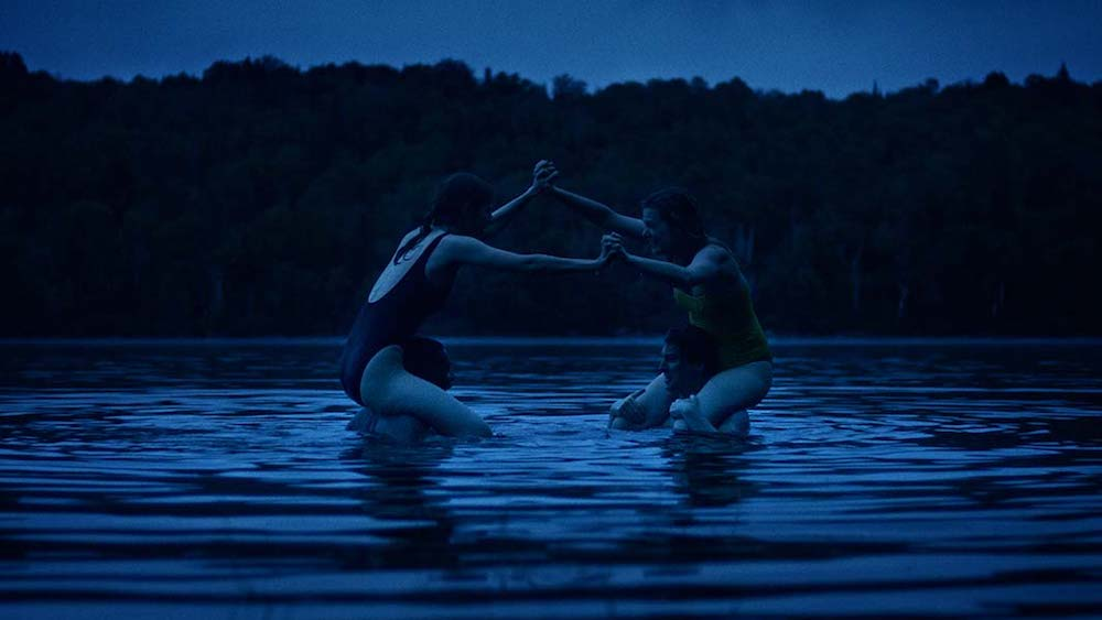 A still from 'Violation'. Two couples are shown in a lake, the entire image is tinted with blue, the two women are on top of the mens shoulders, holding hands over the gap and clearly trying to push one another off their partners.