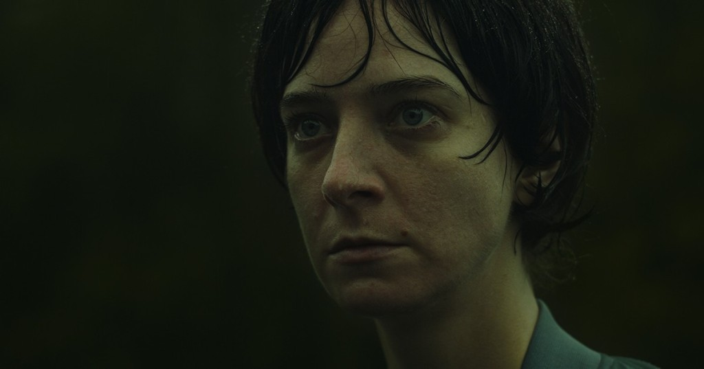A still from 'Violation'. Miriam (Madeleine Sims-Fewer) is shown in close-up, soaked with rain, her face is gaunt, pale and vacant, her eyes piercing. She is a white woman in her 30s, short dark hair and wearing a blue shirt, she has a mole above her lip.
