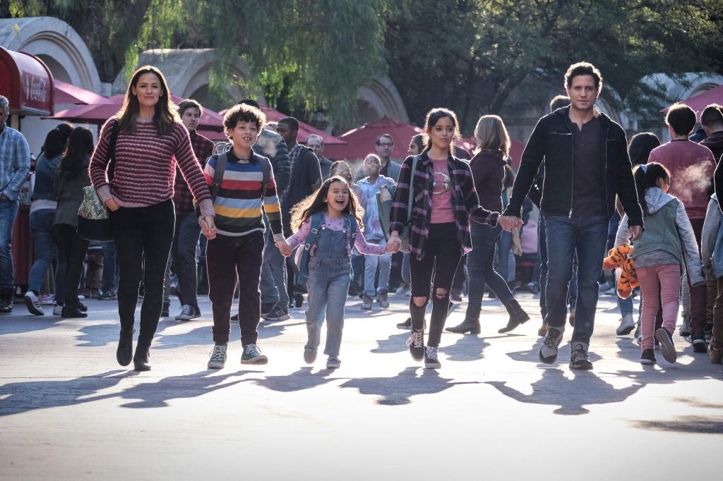 YES DAY. (L-R): JENNIFER GARNER as ALLISON TORRES, JULIAN LERNER as NANDO TORRES, EVERLY CARGANILLA as ELLIE TORRES, JENNA ORTEGA as KATIE TORRES, EDGAR RAMIREZ as CARLOS TORRES. The all hold hands as they walk down a park