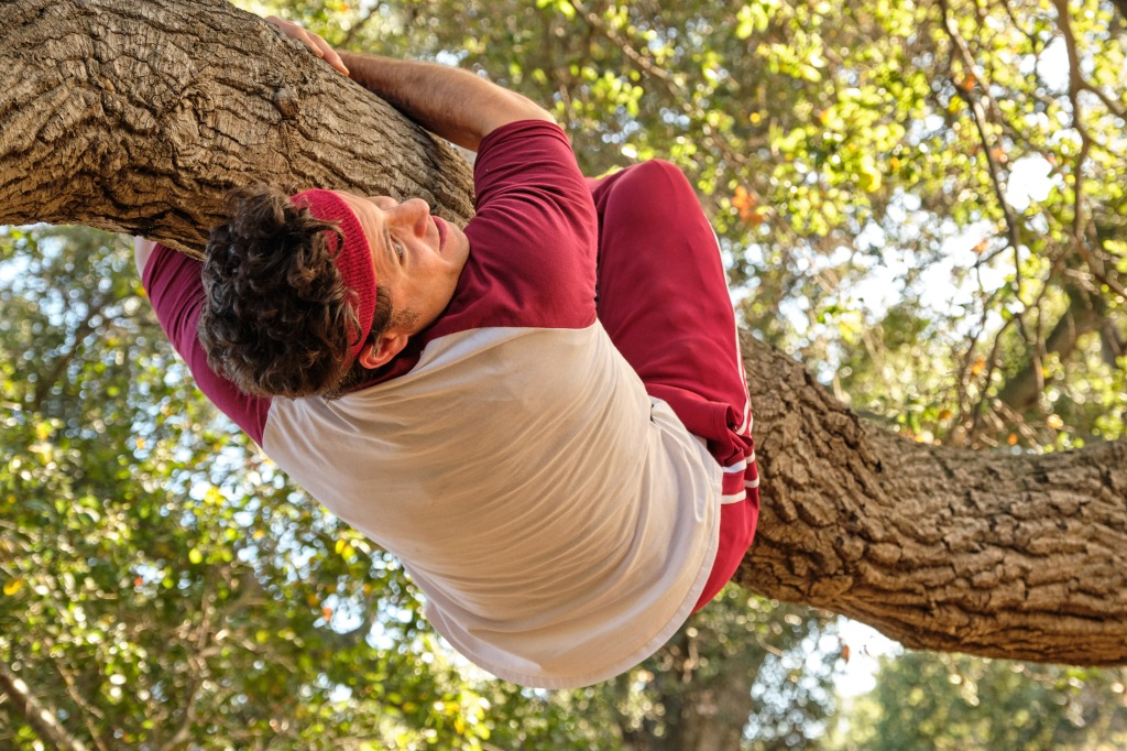 Edgar Ramirez in Yes Day. Dressed in a White long sleeve baseball shirt with read sleeved with matching red pants and sweatband on his forehead. He is holding onto a tree branch with his arms and legs.