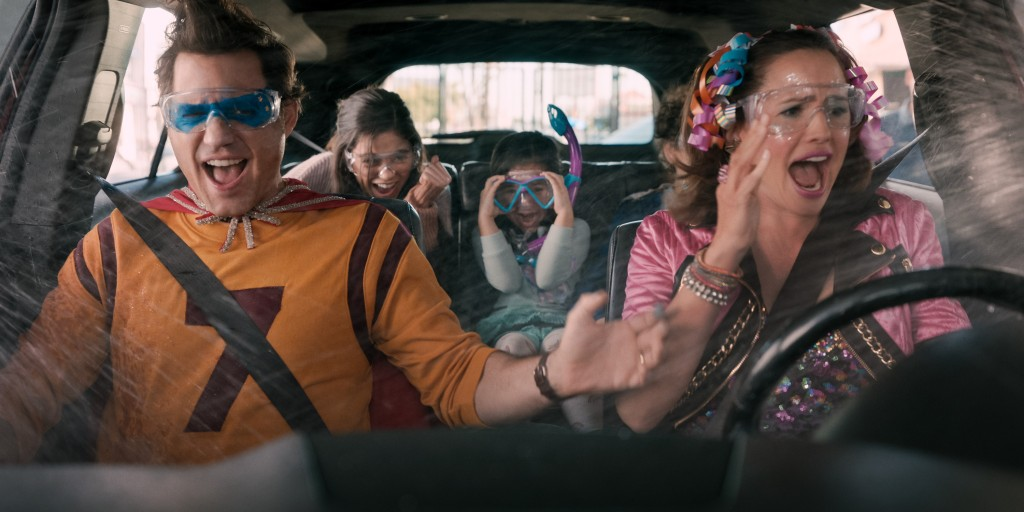 Cast of Yes Day. Edgar Ramirez and Jennifer Garner in the front seats of a car. They are dressed in bright and colourful costumes. Edgar is. dressed as a generic superhero and Jennifer is in a pink get-up with ribbons and bows in her hair. They both where goggles as teh car drives through a car wash with open windows. The child actors are in the back seats.