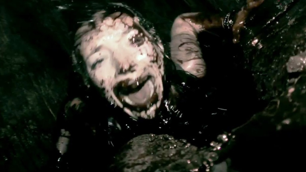 A still from 'As Above So Below'. Scarlett (Perdita Weeks) is shown centre frame in a blurred 'found footage' shot. She is covered in black liquid, deep in a cave, screaming in fear and pain. The image is dark and dingy aside from her pale skin, you can barely tell she's human.