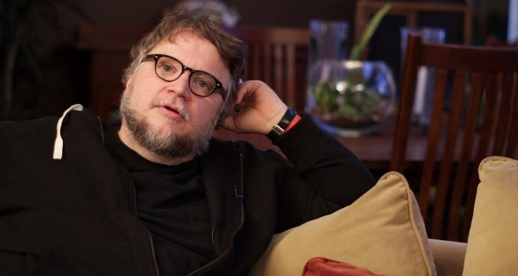 A still from documentary 'Clapboard Jungle'. Director Guillero Del Toro is pictured to the left of the image, in close up, being interviewed. He sits on a couch with his arm resting on the back, wearing a black T-Shirt and hoodie and thick black glasses.
