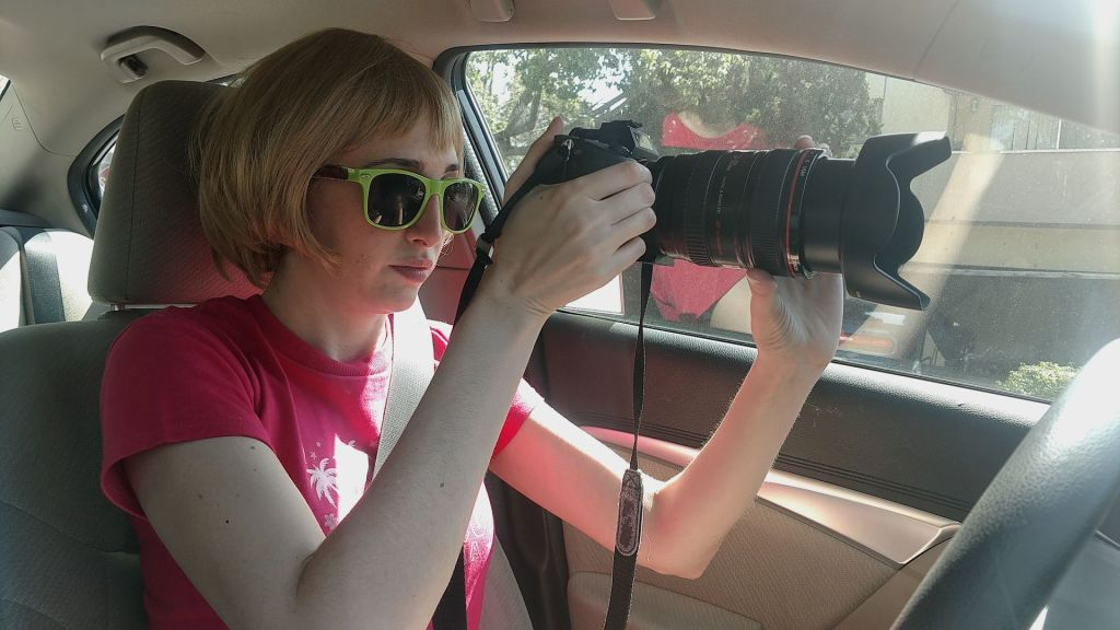 A still from 'I Blame Society'. Gillian (Gillian Wallace Horvat) is shown in close-up, in her car, with a long-lens camera pointing out the widescreen. She is wearing a pink T-Shirt, blonde bob wig and green sunglasses.