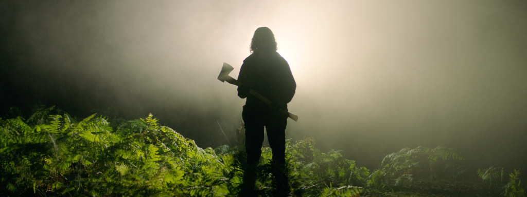 A still from 'In The Earth'. A silhouette of a long-haired figure is seen holding an axe, lights shine brightly behind them in a leafy environment.